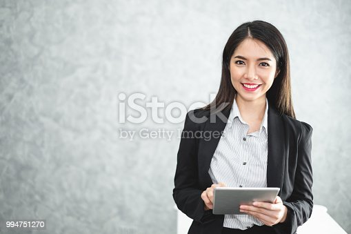 Portrait young Asian businesswoman holding tablet/smartphone in formal suit in office with copy space