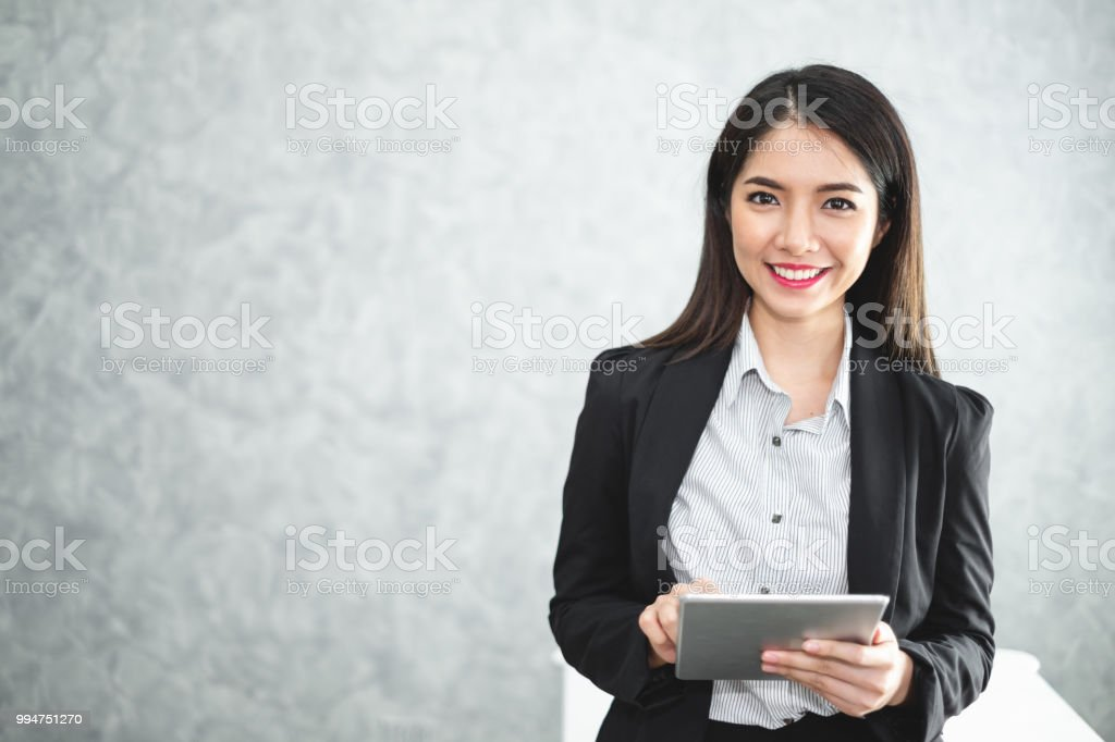 Portrait young Asian businesswoman holding tablet/smartphone in formal suit in office with copy space stock photo