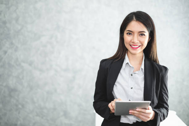 portrait young asian businesswoman holding tablet/smartphone in formal suit in office with copy space - ásia imagens e fotografias de stock