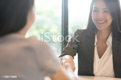 Portrait young Asian woman interviewer and interviewee shaking hands for a job interview .Business people handshake in modern office. Greeting deal concept