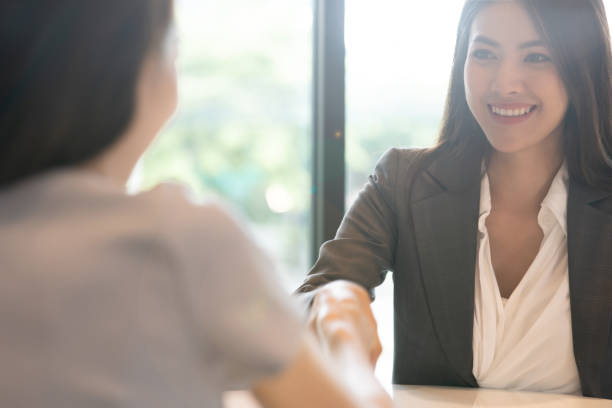 porträtt ung asiatisk kvinna intervjuare och intervjuade skakar händer för en anställnings intervju. affärs män hand skakning i moderna kontor. hälsning deal-konceptet - job interview bildbanksfoton och bilder