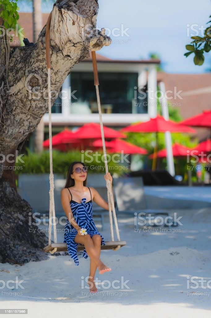 Portrait young asian woman sitting on swing rope and sea around beach...