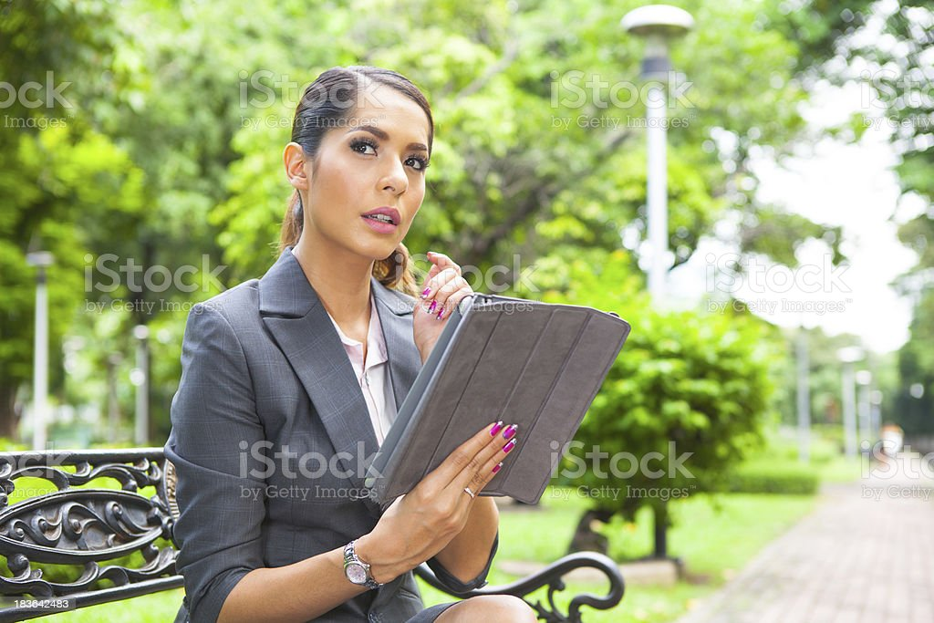 Portrait young attractive businesswoman working with digital tablet at park royalty-free stock photo