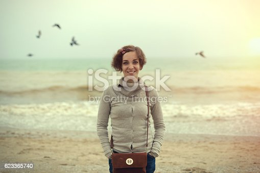 509923232 istock photo portrait young beautiful woman with leather bag on the  beach 623365740
