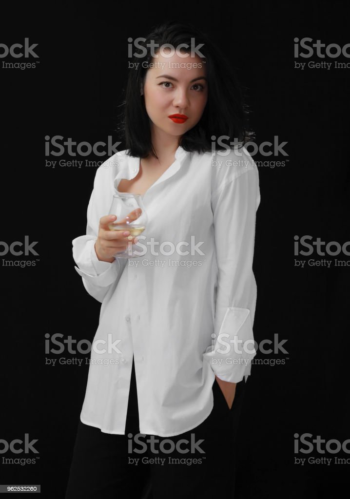 Portrait young brunette beauty holding glass of wine in white shirt on black background. - Royalty-free Adult Stock Photo