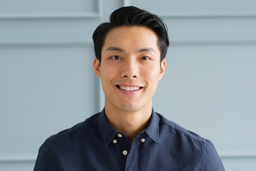 Portrait young confident smart Asian businessman look at camera and smile