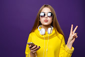 istock Portrait young girl teenager with earphones and phone, in a yellow sweater, isolate on a violet background. 866657418