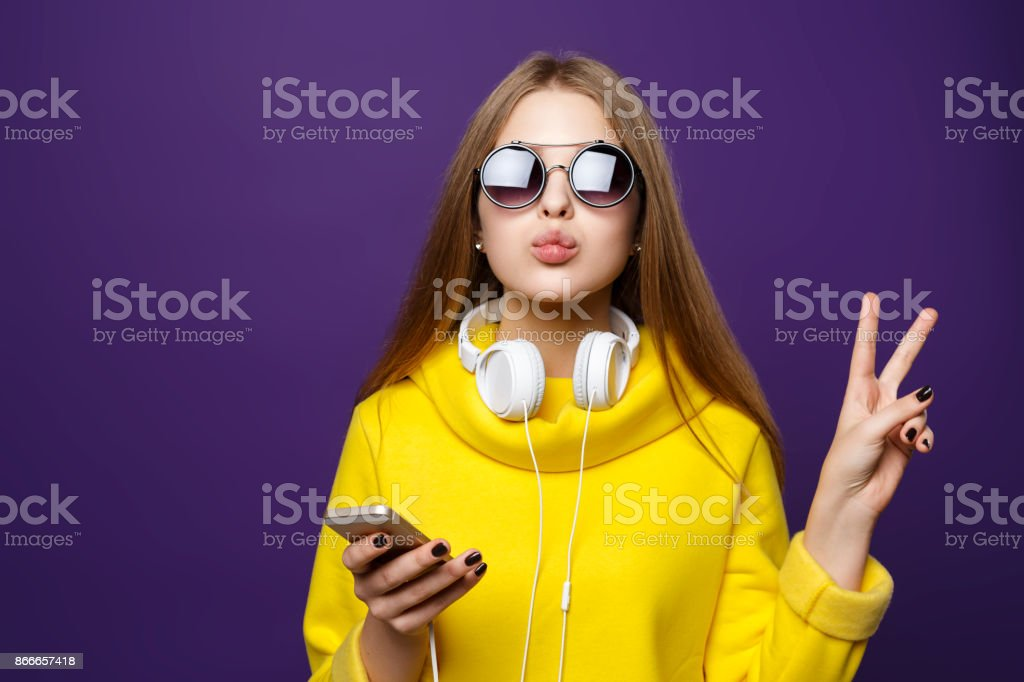 Portrait young girl teenager with earphones and phone, in a yellow sweater, isolate on a violet background. stock photo