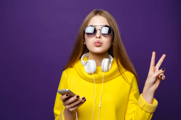 portrait young girl teenager with earphones and phone, in a yellow sweater, isolate on a violet background. - ragazzi adolescenti foto e immagini stock