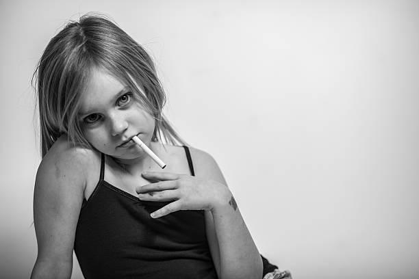 porträt der jungen frau mit zigarette im mund, blick in die kamera - lungenkrebs tattoos stock-fotos und bilder