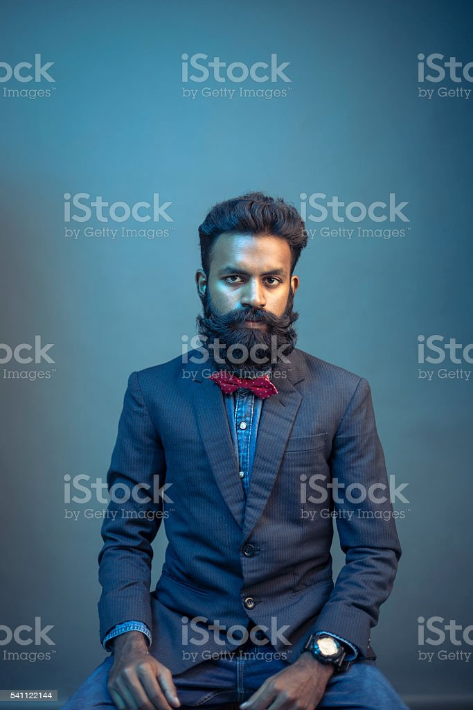 portrait young man posing with beard in suit stock photo