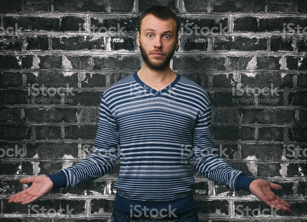 portrait young man shrugging shoulders stock photo