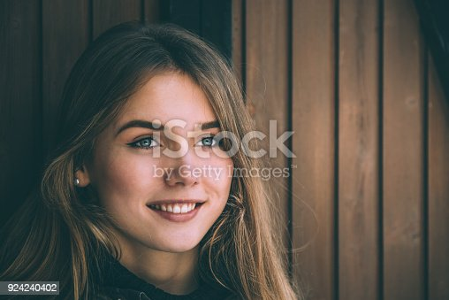 istock portrait Young pretty woman in winter in a log cabin in the snow 924240402