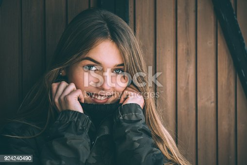 istock portrait Young pretty woman in winter in a log cabin in the snow 924240490