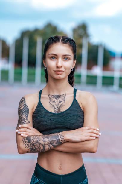 porträt junges sportlich schönes mädchen in katzentattoos, am morgen vor dem fitnesstraining, sportbekleidung top. sommer im stadttraining. emotionen der zuversicht, mut, kraft und ausdauer, glückliches lächeln. - gymnastik tattoo stock-fotos und bilder
