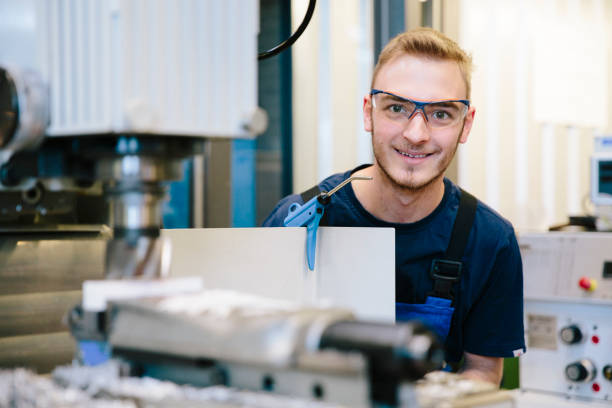 portrait: young technician with protective eyewear works at a milling machine stock photo