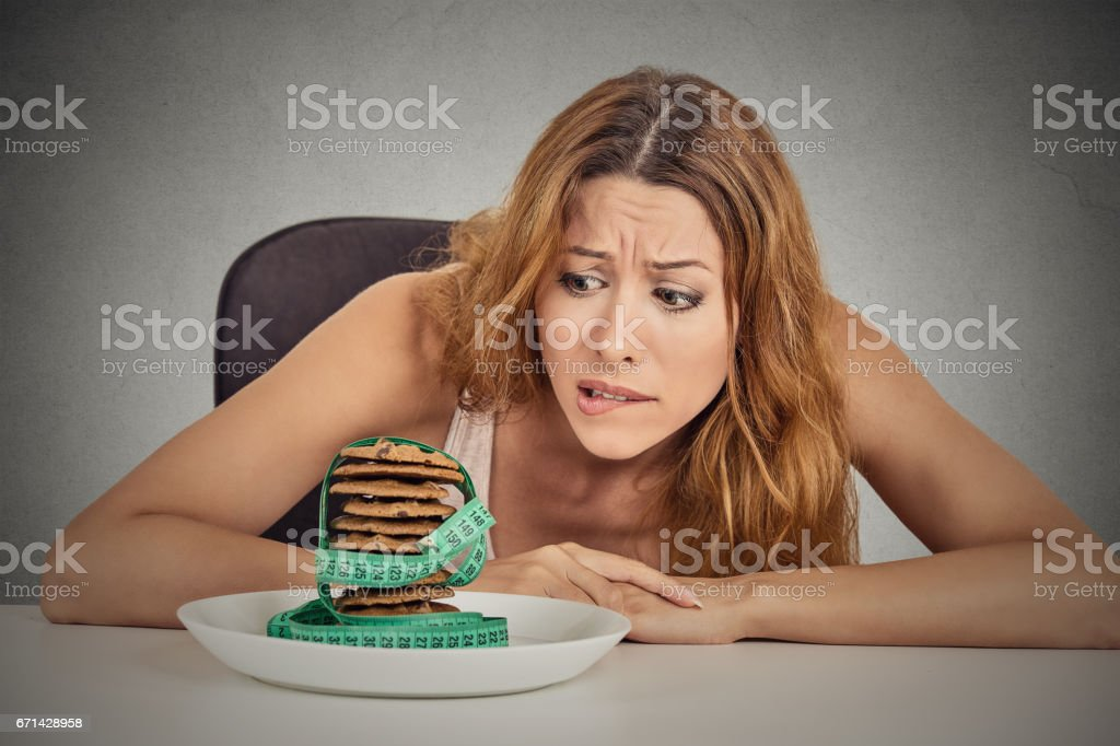 Portrait young unhappy woman craving sugar sweet cookies but worried about weight gain sitting at table stock photo