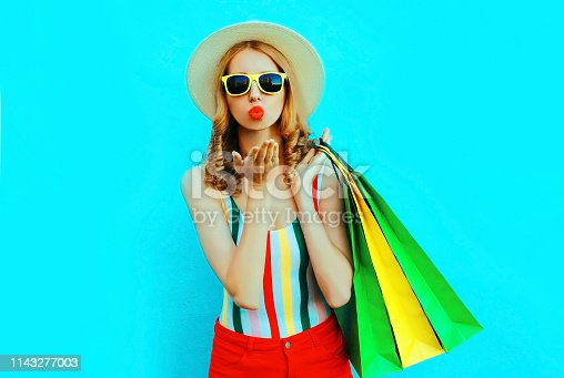 615594632 istock photo Portrait young woman blowing red lips sends air kiss with shopping bags in colorful t-shirt, summer round hat on blue wall background 1143277003