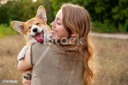 istock Portrait: young woman with laughing corgi puppy, nature background 1276788283