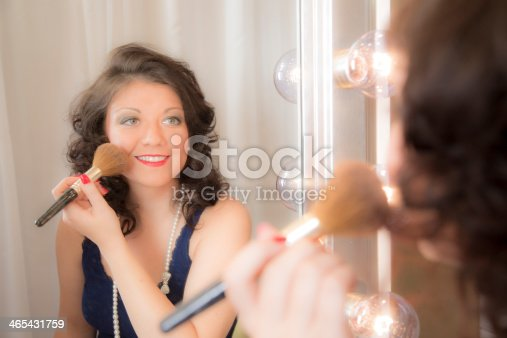 109721176istockphoto Portrait:  Young woman's reflection in a hollywood make-up mirror. Cosmetics. 465431759