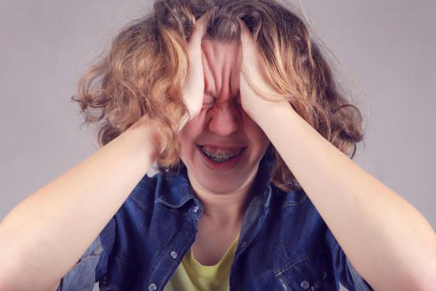 portraite of beautiful teenage girl suffering from severe headache, pressing fingers to temples. - portraite woman foto e immagini stock