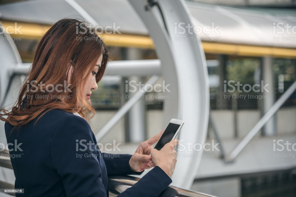 Portraits of beautiful asian woman look confidence is holding cellphone . she using smartphone messaging to conversation with customer. stock photo