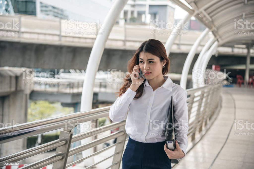 Portraits of beautiful asian woman look confidence is standing and holding cellphone . she using smartphone calling to conversation with customer. stock photo