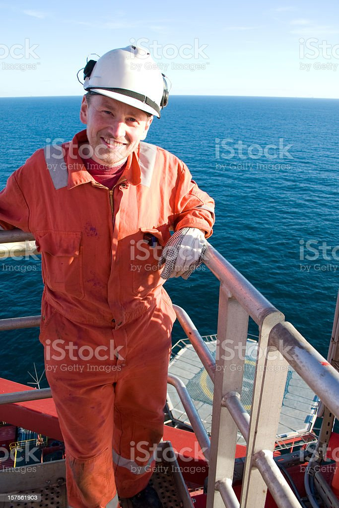 Portraits of man in orange jumpsuit on an oil rig royalty-free stock photo