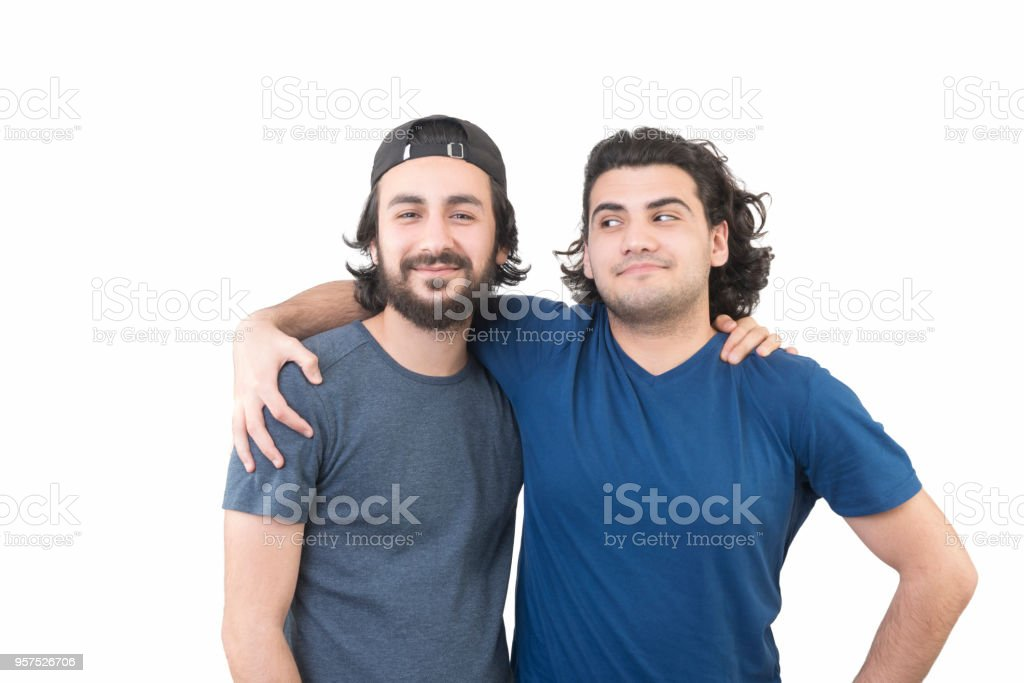Portraits of two male friends looking at camera by hugging each other over white background stock photo