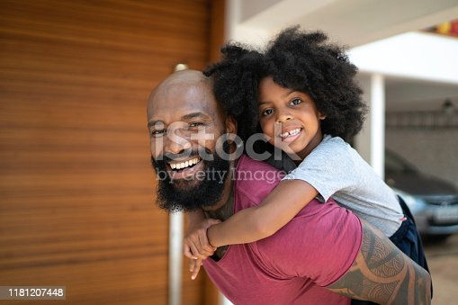 Portrat of father giving his daughter a piggyback ride