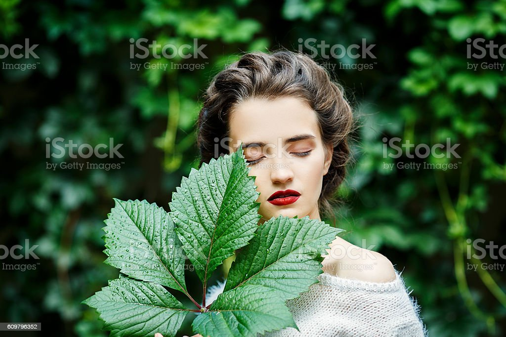 Portreit of young girl with grape leaf in her hand - Photo