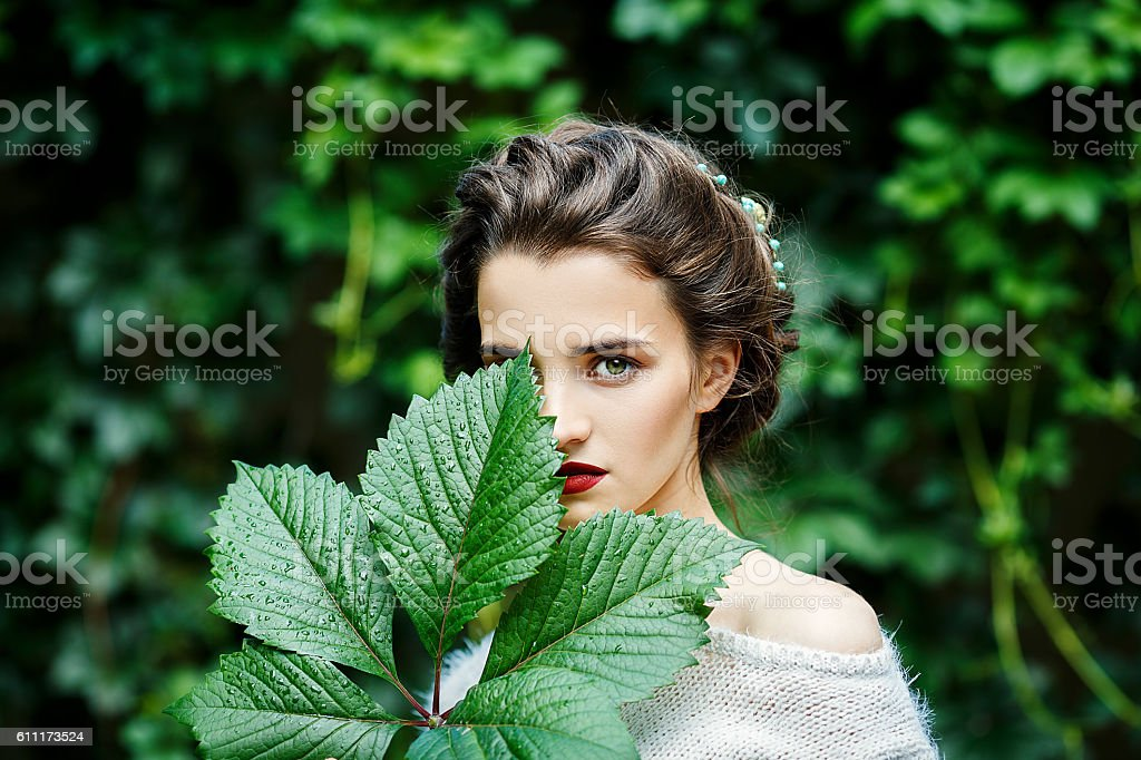 Portreit of young girl with grape leaf in her hand - 免版稅人的嘴唇圖庫照片