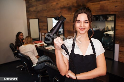istock Portret of smiling hairdresser in beauty salon. Beautiful woman in black apron looking at camera and holding professional hair dryer. Beauty and people concept 1136599956
