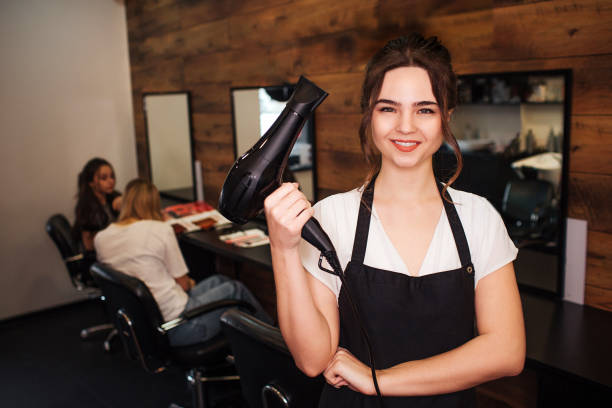 portret of smiling hairdresser in beauty salon. beautiful woman in black apron looking at camera and holding professional hair dryer. beauty and people concept - hairdresser стоковые фото и изображения