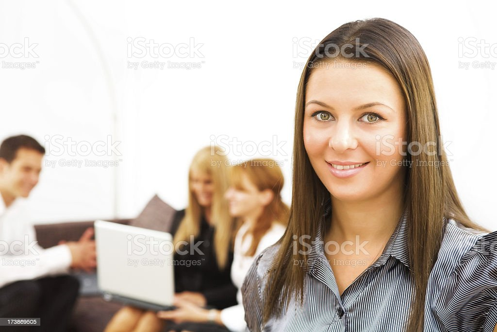 Portret of young business woman (collegues working in the background) royalty-free stock photo