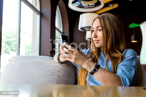 660639880 istock photo Portret of young female reading sms on the phone in cafe. Toned. Selective focus 842468656