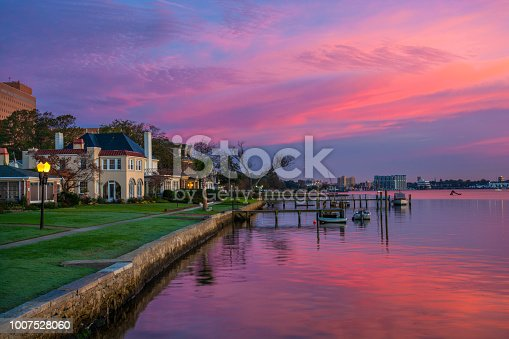 Houses and Riverfront of the Elizabeth River in Portsmouth, Virginia during dawn with magenta, purple, and pink clouds.  Portsmouth, VA is part of the Virginia Beach / Hampton Roads metropolitan area.