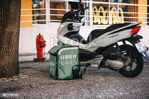 istock Portugal, Lisbon 29 april 2018: Food delivery Uber eats. Motorcycle and on the ground the basket of food that says Uber eats 981709762
