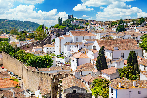 Portugal, Oeste region -    The old town Obidos, surrounded by a fortress wall and towers, view from above. Blue sky with fluffy clouds is on the background.
