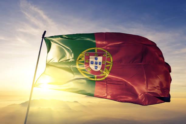 portugal portugees vlag textielweefsel doek zwaaien op de bovenste zonsopgang mist mist - portugal stockfoto's en -beelden