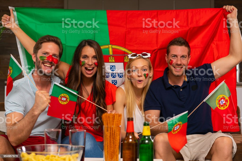portugese soccer fans - with flag of portugal celebrating their team...