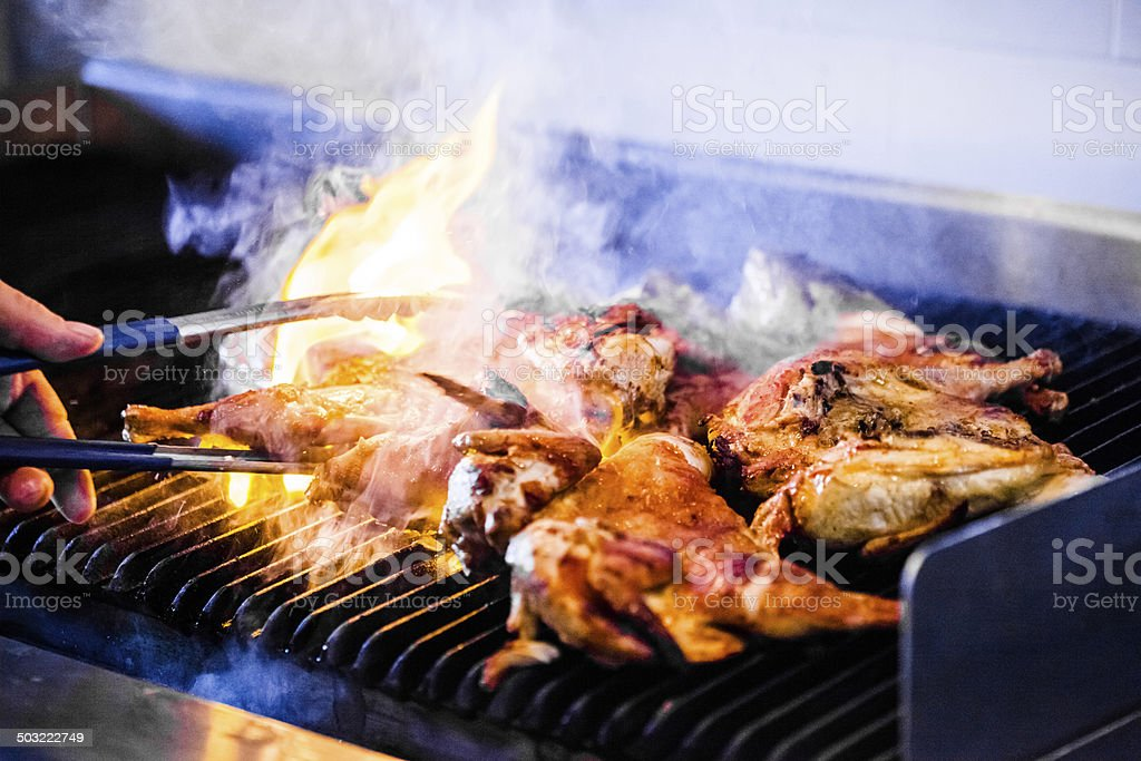 Portuguese Chicken on the Grill Portuguese Chicken Flaming on the Grill Animal Stock Photo