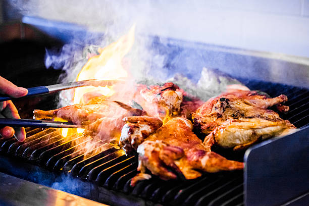 Portuguese Chicken on the Grill Portuguese Chicken Flaming on the Grill chicken stock pictures, royalty-free photos & images