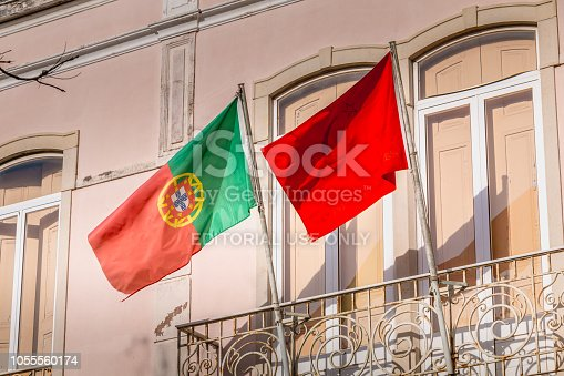 istock Portuguese flag and communist party flag on a building facade 1055560174