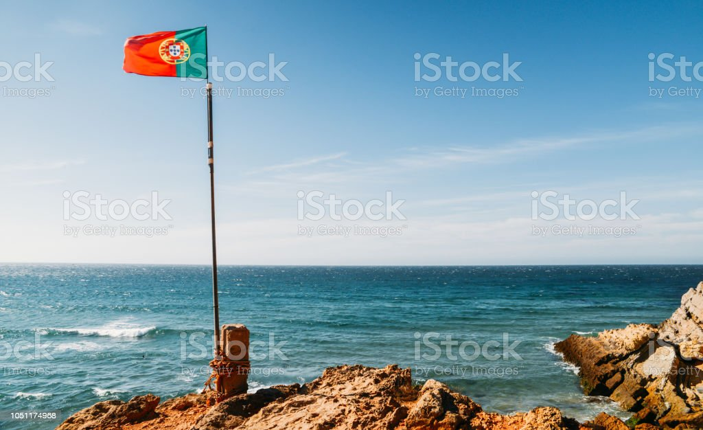 Portuguese flag waving next to sea on a summer day with copy space - fotografia de stock