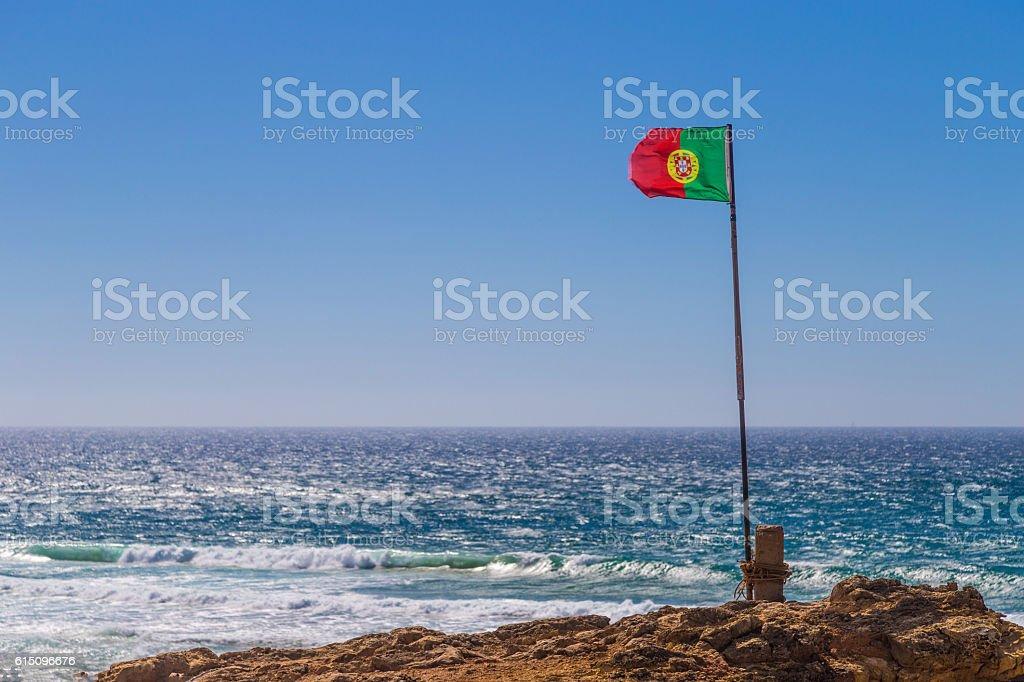 Portuguese flag waving over blue sky and ocean, Guincho Beach - foto de acervo