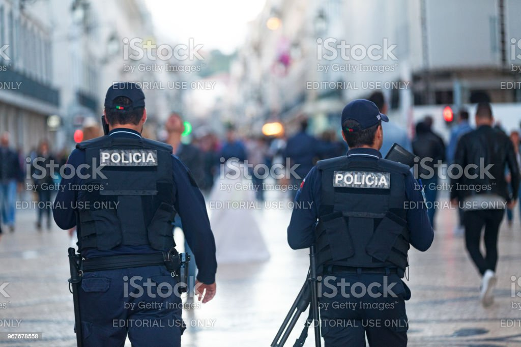 Portuguese policemen in Lisbon Lisbon, Portugal - June 01 2018: Two policemen patrolling the street of the old town. Adult Stock Photo