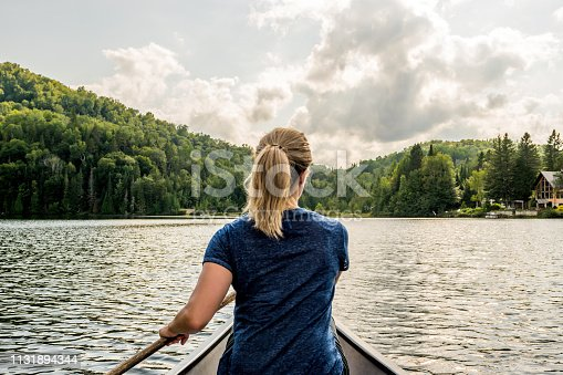 Portuguese woman paddling a canoe with an old wooden oar on a peaceful fishing lake of Quebec with mountain range in background.