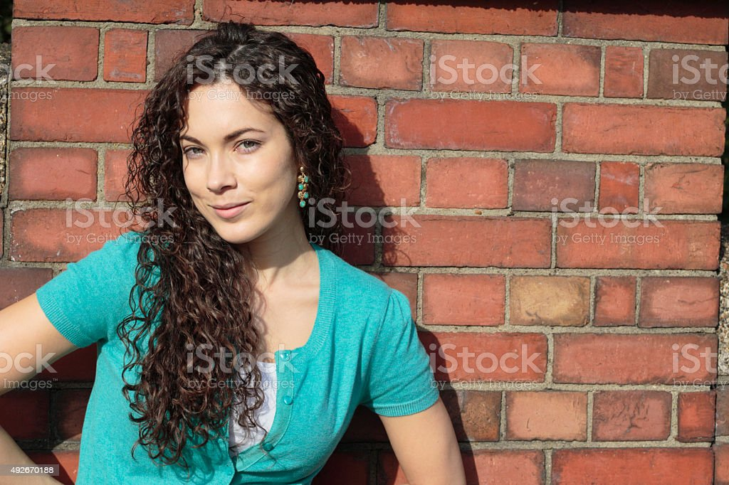Shapely Canadian outdoor girl posed against brick wall stock photo