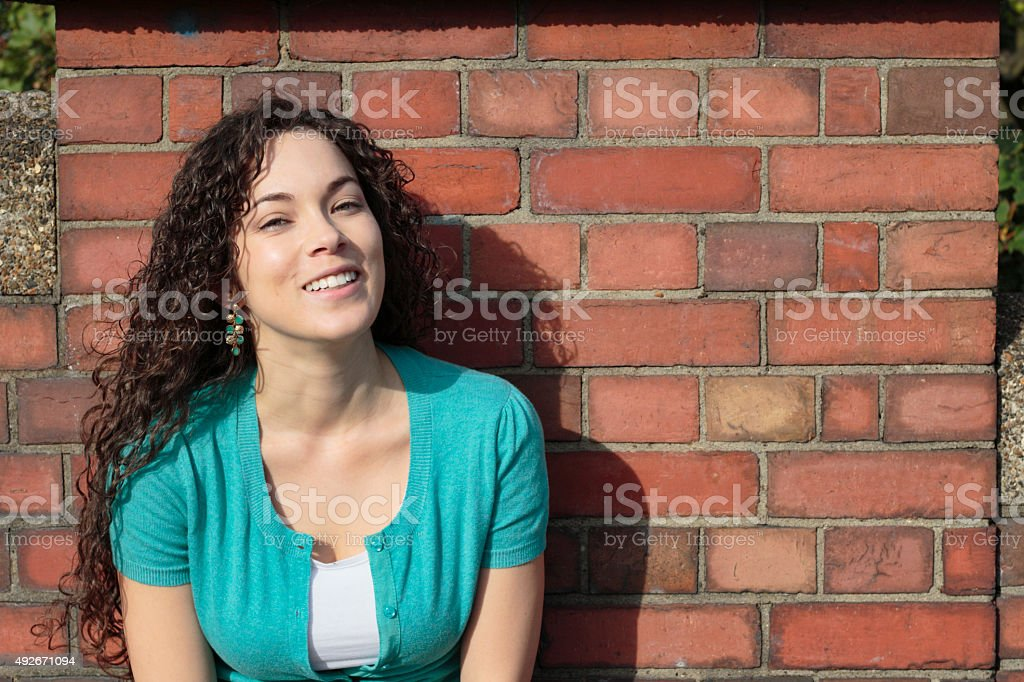 Smiling shapely Canadian outdoor girl posed against brick wall stock photo